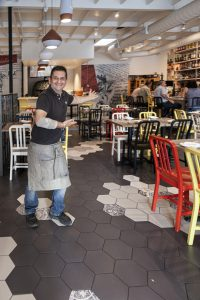 Host Michele Auriemma welcoming guests into Solunto Restaurant & Bakery in Little Italy.